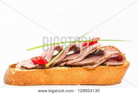 Delicious italian bruschetta with roast beef and fresh scallions. Macro. Photo can be used as a whole background.
