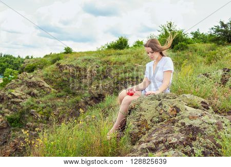 Beautiful young sad woman with long hair, waving in the wind, sitting on the rock in the forest holding ripe red nectarine ** Note: Soft Focus at 100%, best at smaller sizes