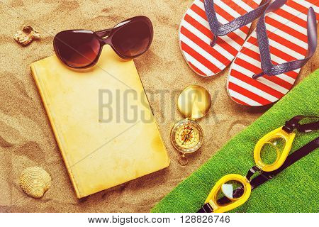 Summer beach holiday vacation accessories on sand surface summertime lifestyle objects in flat lay top view arrangement.