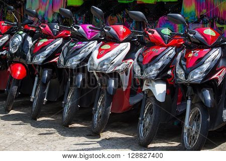 KOH PHANGAN THAILAND - OCTOBER 30 2015: Motorbike parked on the street for rent to tourists