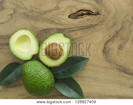 avocado and Sliced avocado on a dark wood background.