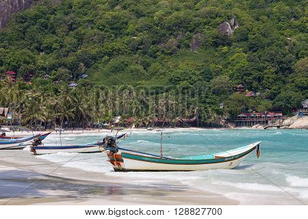 KOH PHANGAN THAILAND - OCTOBER 30 2015: Haad Rin beach after full moon party. Wooden boats waiting for tourists. Thailand attracts many tourists every year
