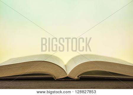 Open book on wood table with abstract light background.