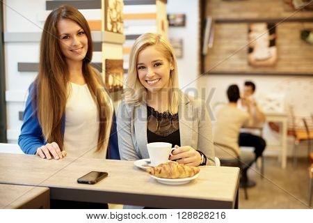 Portrait of happy girls having breakfast in cafeteria, smiling, looking at camera.