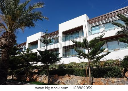 HERAKLION, CRETE, GREECE - MAY 13, 2014: The blue sky modern building of villa with balcones and palms on the terrain of luxury class hotel Grecotel Amirandes on the Mediterranean coast of Crete, May 13, 2014, Greece.