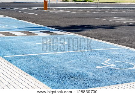 International handicapped symbol painted in bright blue on a shopping center parking space.