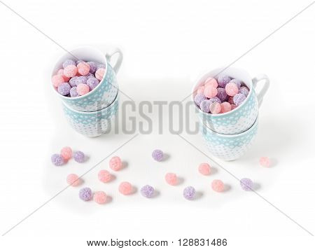 Fruit bonbons in coffee cups on white canvas isolated on white copy space