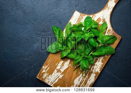 Bunch of fresh mint on a wooden cutting board over dark background