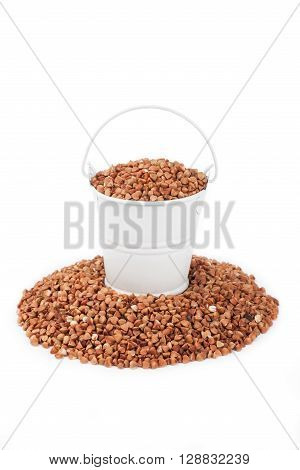 White bucket full of buckwheat stands on a heap buckwheat on a white background