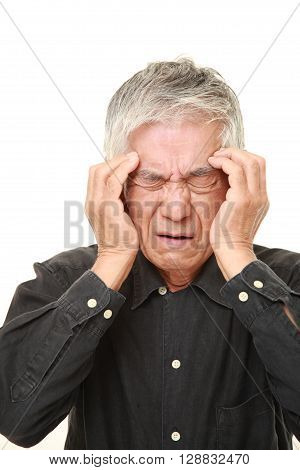 portrait of senior Japanese man suffers from headache on white background