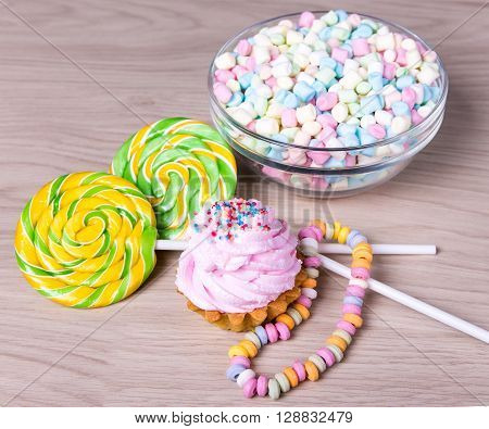 Mini Marshmallows In Glass Bowl, Candies And Cup Cake On Wooden Table