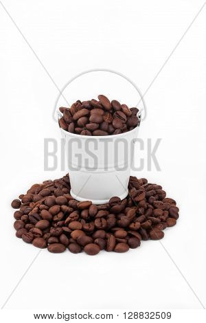 White bucket full of coffee beans stands on a heap coffee beans on a white background