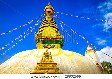 Swayambhunath Stupa with the prayer flags and blue sky at the background.
