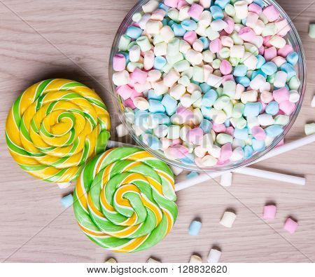 Mini Marshmallows And Lollipops On Wooden Table Background