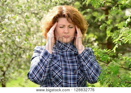 A woman with a headache on the nature of the spring