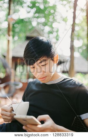 A Man Drinking Morning Coffee In Sunshine Light Reading Good News On Mobile Phone