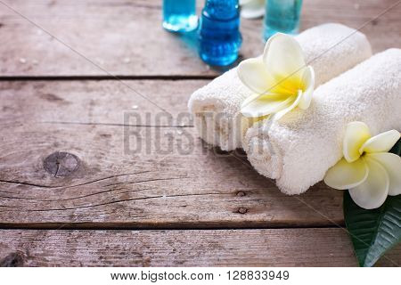 Spa or wellness setting. Towels bottles with oil and white plumeria flowers on wooden background. Selective focus. Place for text.