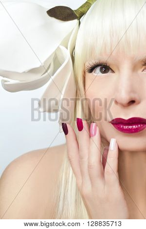 Makeup and colored maroon manicure on a girl, blonde with flower on the head.