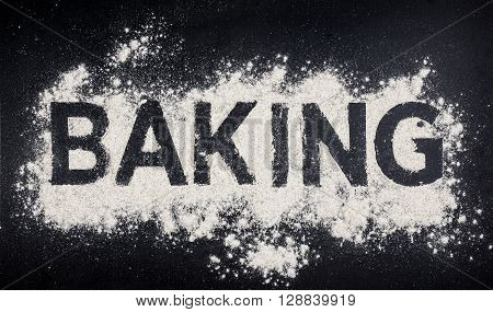 Baking word made from white flour on dark table, baking store logo.