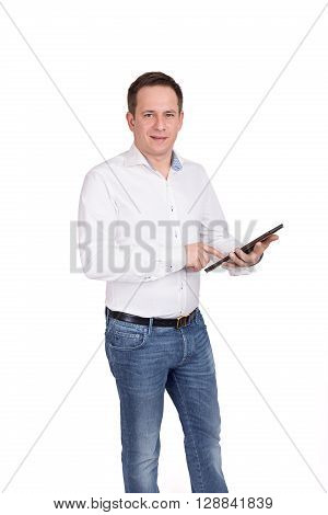 Successful Young Businessman On A White Background In A White Shirt And Blue Jeans Holds Tablet Devi