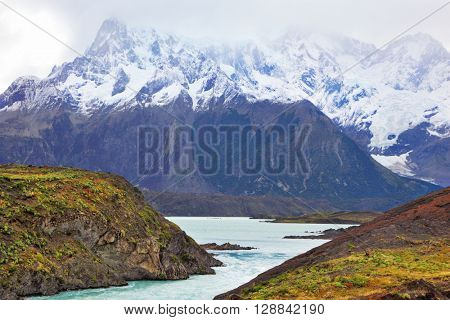 Neverland Patagonia. Snow-capped mountains of the national park Torres del Paine. Icy emerald water of the mountain river flows between hills