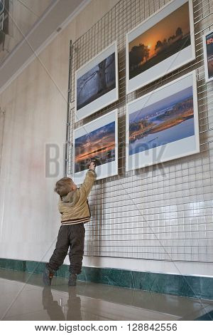 RECHITSA, Belarus - April 20, 2016: A boy at ease behaves photo pictures at an exhibition in the cultural center of Black Gold.