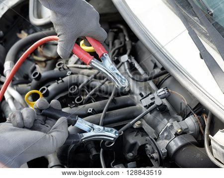mechanic working on a car engine using electrical cables