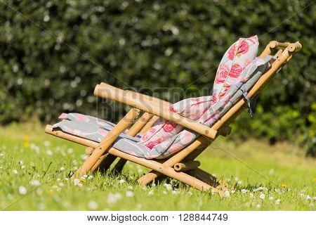 Rattan sun deck chair with pillows