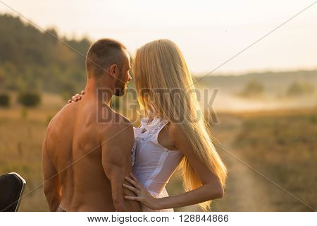 Man and woman embrace tenderly in the field. Love and sincere feelings. Beautiful young couple. Photo for social magazines posters and websites.