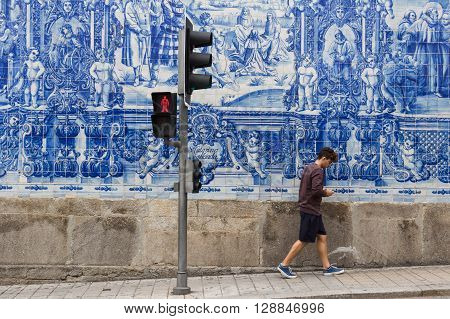 Guy Walking Along A Typical Portuguese Decorated Wall