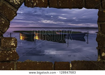 View of boats at sunset through a breach in an old brick wall