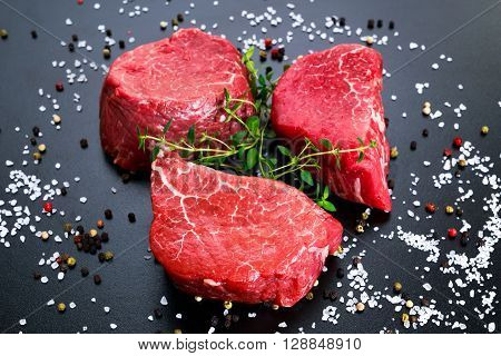 Fresh Raw Beef Filet Mignon, with salt, peppercorns and thyme. Ready to cook