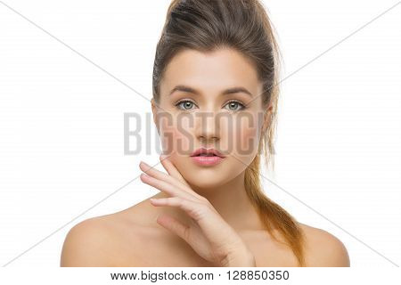 Beautiful young woman with soft skin and hair in ponytail. Beauty shot. Isolated over white background. Copy space.