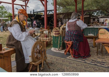 Women With Medieval Costumes Working With Fabric