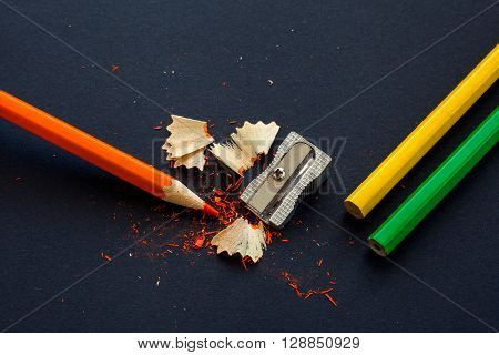 sharpener and wooden pencils with particles of sharpening on black