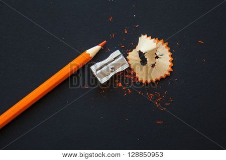 sharpener and orange wooden pencil with shavings on black