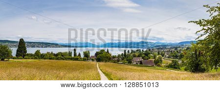 Panorama view of Zurich lake and the alps on the hill of the peninsula Au located in the lake Zurich at the municipality Au between Wadenswil and Horgen in the Canton of Zurich Switzerland.
