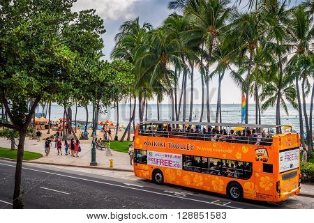 Honolulu, Hawaii, USA - Dec 15, 2015: Waikiki tourist shuttle bus parked along Kalakaua Avenue, near the Kuhio Beach Hula Mound, Waikiki Beach area. This is an affordable form of transport and is popular among tourists.
