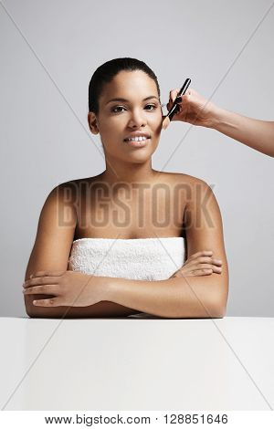 Black Woman With A Basic Makeup And Hand Os Makeup Artist With A Foundation Brush