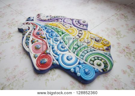 hand-molding khamsa from polymer clay  on a wooden base
