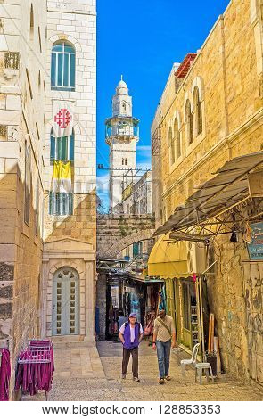 JERUSALEM ISRAEL - FEBRUARY 18 2016: The narrow market street with the white stone minaret of the Omar Mosque on the background on February 18 in Jerusalem.