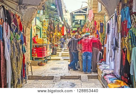 JERUSALEM ISRAEL - FEBRUARY 18 2016: The company of merchants stands in a close circle and plays the dice in Arab Bazaar on King David's street on February 18 in Jerusalem.