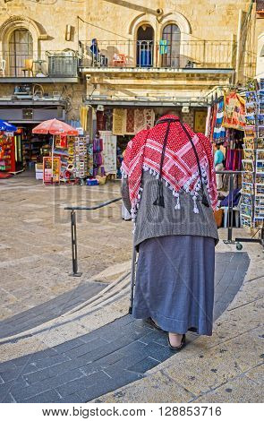 JERUSALEM ISRAEL - FEBRUARY 18 2016: The senior Palestinian in traditional red kufiya and galibaya in Omar Ben el-Hatab street on February 18 in Jerusalem.