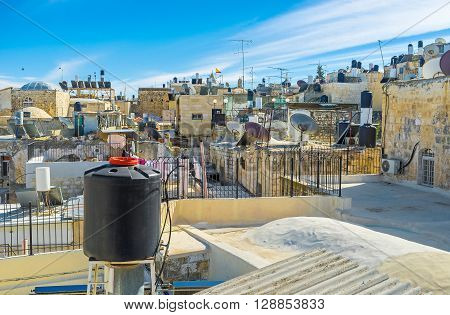 All the city roofs are occupied by black and white water storage tanks and different satellites Jerusalem Israel.