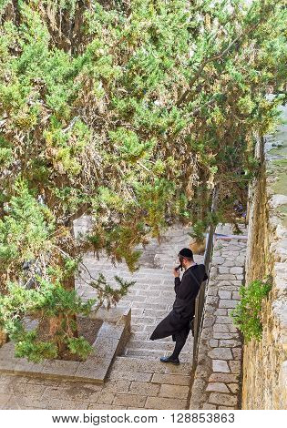 JERUSALEM ISRAEL - FEBRUARY 18 2016: The young hasid relax in shade of the lush pine leaning on the medieval wall on February 18 in Jerusalem.