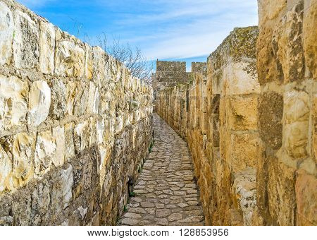 The narrow stone way betwwen the walls on the top of the medieval rampart of Jerusalem Israel.