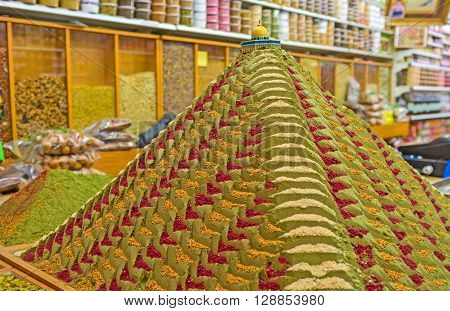 The pyramid made of colorful spices with the figure of the Dome of the Rock decorates the old spice shop in Muslim Quarter of Jerusalem Israel.