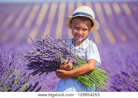 Happy boy in hat with big bouquet in lavender summer field near Valensole. Provence, France.