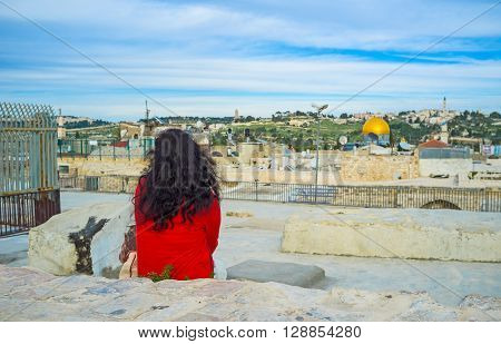 The lonely girl sits on the roof of Jerusalem's house and watches the views thinking about eternity Israel.