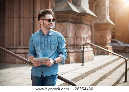 Contemporary view. Cheerful pleasant handsome guy holding tablet and leaning on the handrail while expressing gladness